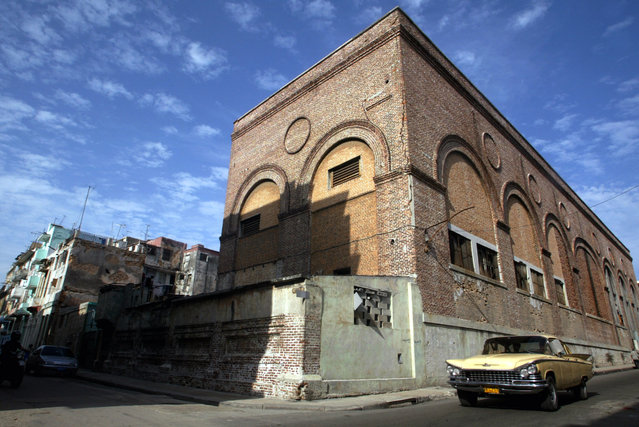 A vintage car drives past a building in Havana, August 4, 2006. (Photo by Enrique De La Osa/Reuters)