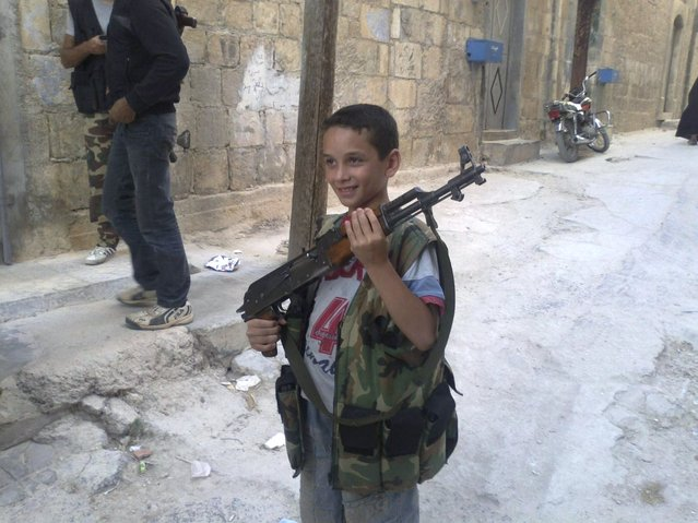 A boy poses with a rifle in Kafr Takharim, on the outskirts of Idlib July 17, 2012. Picture taken July 17, 2012. (Photo by Reuters/Shaam News Network)