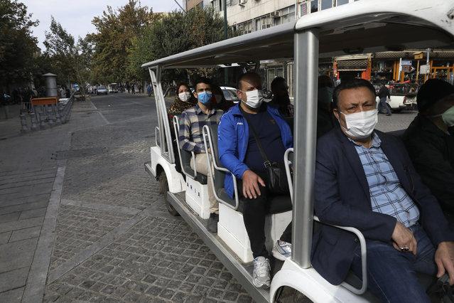 Passengers ride an electric minibus shuttle at Tehran's Grand Bazaar, Iran, Sunday, November 8, 2020. (Photo by Vahid Salemi/AP Photo)