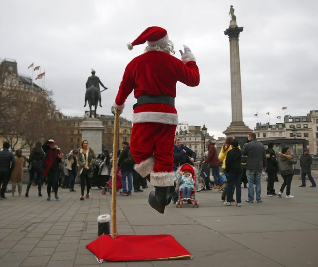 A man dressed as Father Christmas appears to levitate by using a specially-designed prop and costume as he waves to people in Trafalgar Square in central London December 22, 2014. (Photo by Eddie Keogh/Reuters)
