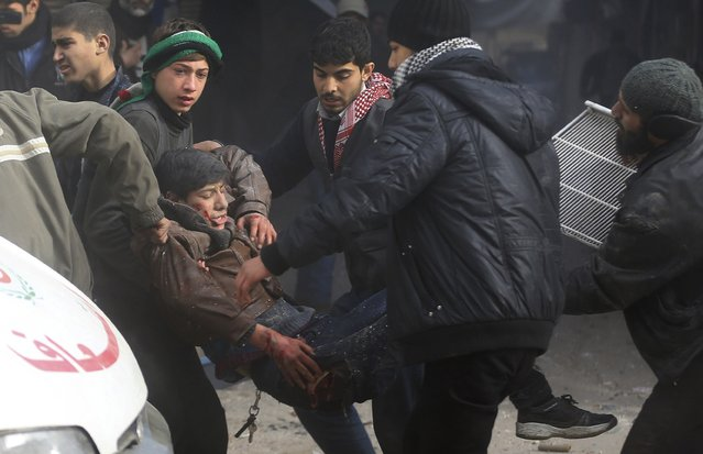 People rescue an injured civilian at a site hit by what activists said was an air strike by forces of Syria's President Bashar al-Assad in the Duma neighbourhood of Damascus December 27, 2014. (Photo by Bassam Khabieh/Reuters)