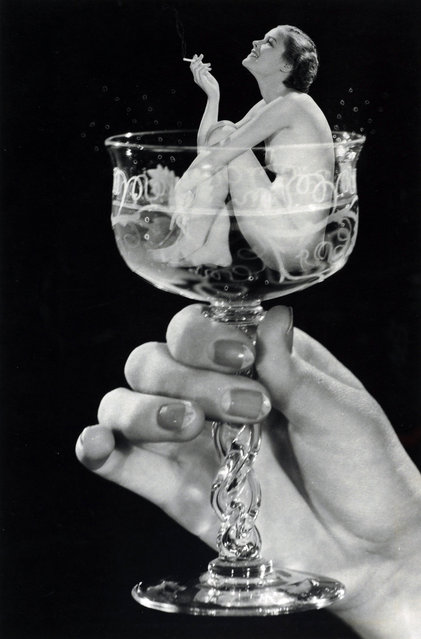 """Woman in Champagne Glass"" by Howard S. Redell, ca. 1930. Redell, a photographer and sales manager at Underwood and Underwood Studios, harnessed the power of s*x appeal in this photomontage of an attractive young woman enjoying a cigarette while bathing in a glass of champagne – a pictorial fantasy of luxury and indulgence that was probably created as a tobacco advertisement. (Photo courtesy of The Metropolitan Museum of Art)"