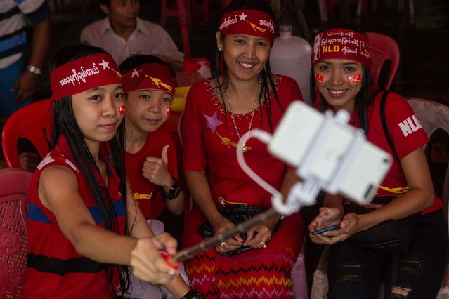 A group of opposition supporters take a selfie as hundreds of people gather outside the opposition party headquarters despite rain in Yangon, Myanmar, Monday, November 9, 2015. With tremendous excitement and hope, millions of citizens voted Sunday, Nov. 8 in Myanmar's historic general election that will test whether the military's long-standing grip on power can be loosened, with opposition leader Aung San Suu Kyi's party expected to secure an easy victory. (Photo by Amanda Mustard/AP Photo)
