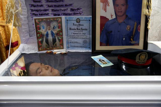 The body of policeman Rancel Cruz, whom police investigators said was shot dead by a drug addict, lies in a coffin in Manila, Philippines, October 19, 2016. (Photo by Erik De Castro/Reuters)