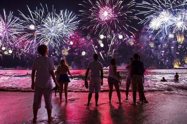 People watch fireworks exploding over Copacabana beach during New Year celebrations in Rio de Janeiro, Brazil, Thursday, January 1, 2015. (Photo by Felipe Dana/AP Photo)