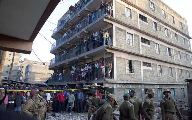 Kenyans watch rescue workers from a nearby building at the site of the collapsed building in the capital Nairobi, Kenya , Monday, January 5, 2015. (Photo by Sayyid Azim/AP Photo)