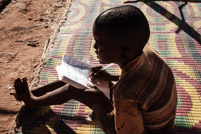 An Ethiopian refugee grade four pupil who fled the Tigray conflict attends a class at a makeshift classroom set by the Norwegian Refugee Council (NRC) at Um Raquba refugee camp in Gedaref, eastern Sudan, on December 7, 2020. The Norwegian Refugee Council (NRC) has registered 722 students from grades one through ten at Um Raquba refugee camp. According to the UN refugee agency, 45 percent of the refugees are children. (Photo by Yasuyoshi Chiba/AFP Photo)