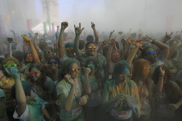 Participants covered in colored powder celebrate after running the Color Manila Run in Taguig City, metro Manila January 4, 2015. Hundreds of runners joined the annual event, which aims to promote a healthier lifestyle. (Photo by Romeo Ranoco/Reuters)