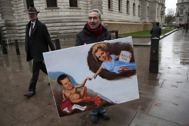 Artist Kaya Mar holds a painting depicting Chancellor George Osborne and former Prime Minister Margaret Thatcher, outside of Britain's Treasury building in central London, Britain November 25, 2015. British finance minister George Osborne will set out on Wednesday his plans for deep spending cuts in many areas of the government and in welfare as he seeks to turn the country's big budget deficit into a surplus by the end of the decade. (Photo by Suzanne Plunkett/Reuters)