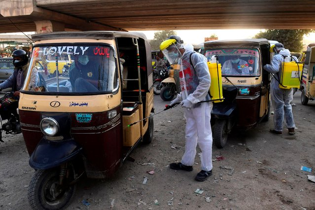 Arsalan Helpline Welfare Trust (AHWT) workers spray disinfectant on auto-rickshaws along a street as a preventive measure against the spread of the Covid-19 coronavirus, in Karachi on December 14, 2020. (Photo by Asif Hassan/AFP Photo)