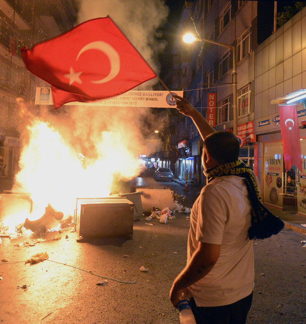 In this photo taken late Saturday, June 1, 2013, a demonstrator waves a national flag as Turkish protesters clash with riot police near the former Ottoman palace, Dolmabahce, where Turkey's Prime Minister Recep Tayyip Erdogan maintains an office in Istanbul, Turkey.  (Photo by AP Photo)
