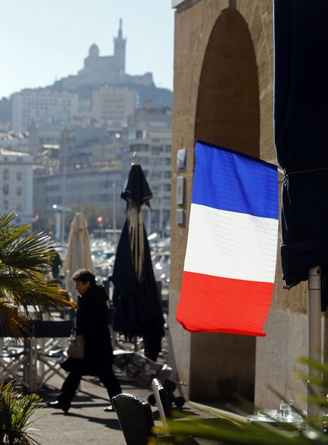 A French national flag hangs over a cafe terrace in Marseille, France, November 27, 2015 as the French President called on all French citizens to hang the tricolour national flag from their windows on Friday to pay tribute to the victims of the Paris attacks during a national day of homage. (Photo by Jean-Paul Pelissier/Reuters)