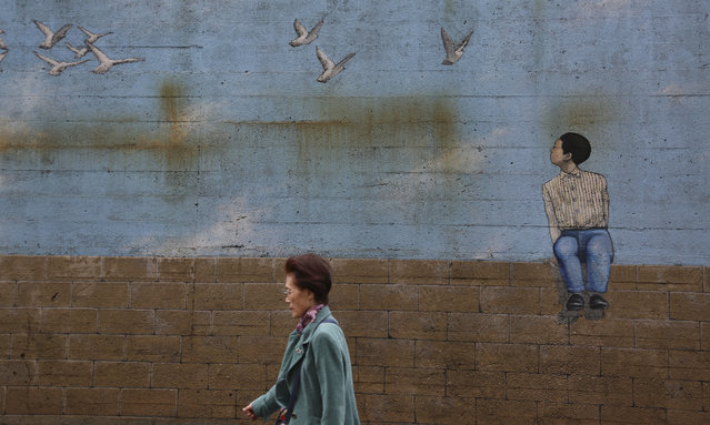 A woman walks past a mural painting on a street in Tokyo, Wednesday, April 25, 2018. (Photo by Koji Sasahara/AP Photo)