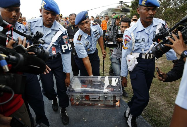 Military policemen carry the flight data recorder of AirAsia QZ8501 at the airbase in Pangkalan Bun, Central Kalimantan January 12, 2015. Indonesian navy divers on Monday retrieved the black box flight data recorder from an AirAsia airliner that crashed two weeks ago, killing all 162 people on board, a government official said. (Photo by Darren Whiteside/Reuters)