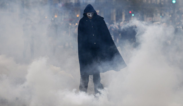 A demonstrator in a mask walks past smoke as demonstators clash with French riot police during on Place de la Republique ahead of the COP21 World Climate Change Conference 2015 in Paris, France, Sunday, November 29, 2015. (Photo by Ian Langsdon/EPA)