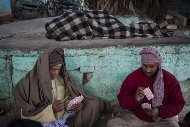 An Indian homeless man sleeps as rickshaw pullers play cards on a cold winter day in New Delhi, India, Wednesday, January 14, 2015. North India continued to reel under cold wave conditions as mercury dipped in several places today with dense fog affecting the movement of traffic, according to local reports. (Photo by Tsering Topgyal/AP Photo)