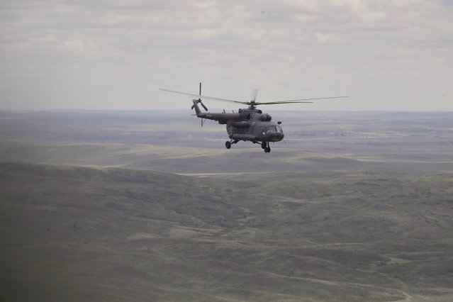 A Russian search and rescue team helicopter flies from the Kazakh town of Karaganda to Dzhezkazgan, on the eve of Russian Soyuz MS space capsule landing, Kazakhstan, Kazakhstan, Sunday, June 3, 2018. The return of the Soyuz space capsule with Russian cosmonaut Anton Shkaplerov, U.S. astronaut Scott Tingle, and Japanese astronaut Norishige Kanai, crew members of the mission to the International Space Station, ISS is scheduled on Sunday, June 3, 2018. (Photo by Dmitri Lovetsky/AP Photo/Pool)