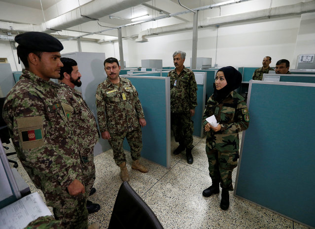 First Lieutenant for the Afghan National Army (ANA), Zainab Baqiri Shayan, 24, speaks with her colleagues in the radio operating department at the Ministry of Defence in Kabul, Afghanistan, October 31, 2016. (Photo by Mohammad Ismail/Reuters)