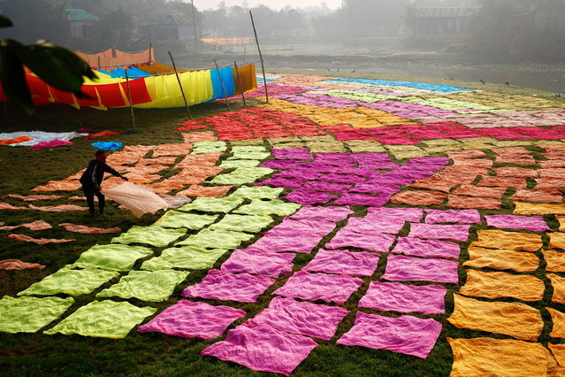 A worker dries fabrics after applying color at a dye factory in Narayanganj, Bangladesh, January 13, 2021. (Photo by Mohammad Ponir Hossain/Reuters)