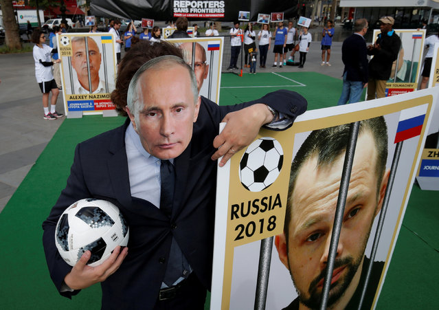 A Reporter Without Borders (RSF) activist, wearing a mask depicting Russian President Vladimir Putin, stands next to a giant portrait of journalist Alexei Kungurov on Place de la Republique, transformed into a soccer field to denounce abuse of press freedom in Russia before the start of the 2018 FIFA World Cup Russia, in Paris, France, June 13, 2018. (Photo by Philippe Wojazer/Reuters)