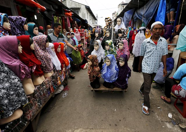 A street vendor (C) pulls a cart with his mannequins during a sweep operation by Civil Service policemen against illegal street vendors, which caused traffic congestion at Tanah Abang market in Jakarta, in this April 7, 2015 file photo. (Photo by Reuters/Beawiharta)