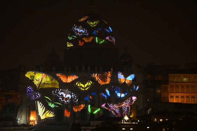 A picture is projected on the facade and the cupola of St. Peters Basilica during the show Fiat Lux : Illuminating Our Common Home, on December 8, 2015 at the Vatican. (Photo by Tiziana Fabi/AFP Photo)