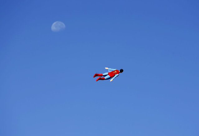 A radio-controlled Superman plane, flown by designer Otto Dieffenbach, passes the moon during a test flight in San Diego, California June 27, 2013. Otto and business partner Ed Hanley are a small start-up company that creates flying radio-controlled planes, designed in the form of people, characters and objects, for commercial and promotional uses. (Photo by Mike Blake/Reuters)
