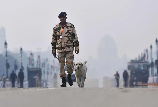An Indian security personnel with a sniffer dog, patrols near India Gate ahead of the Republic Day parade in New Delhi January 23, 2015. (Photo by Anindito Mukherjee/Reuters)