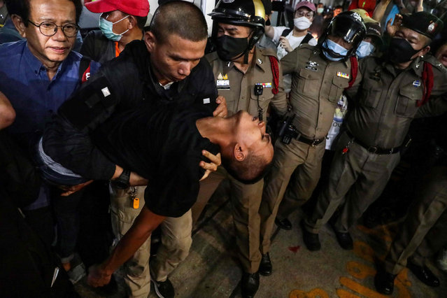 """Pro-democracy activist Panupong """"Mike"""" Jadnok (C) is carried into a hospital vehicle after arriving at Prachachuen police station in Bangkok on October 30, 2020, following his release from the Bangkok Remand Prison. (Photo by Jack Taylor/AFP Photo)"""