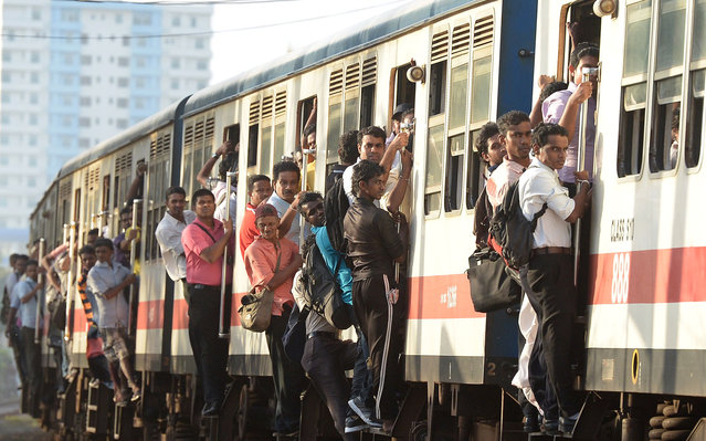 Sri Lankan commuters hold on to the sides of train coaches as they head to work in Colombo on June 29, 2013. (Photo by Lakruwan Wanniarachchi/AFP Photo)