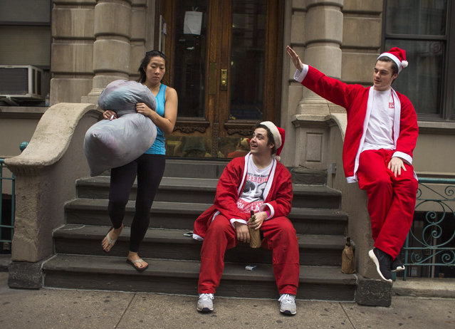 Revelers dressed in holiday theme costumes drink alcohol as a woman comes out with her laundry during SantaCon in New York Saturday, December 12, 2015, in New York. As thousands of Santa-suited merrymakers prepare to hit the city's streets and bars, organizers of the annual pub crawl say they're taking more steps than ever to deter naughty behavior. (Photo by Andres Kudacki/AP Photo)