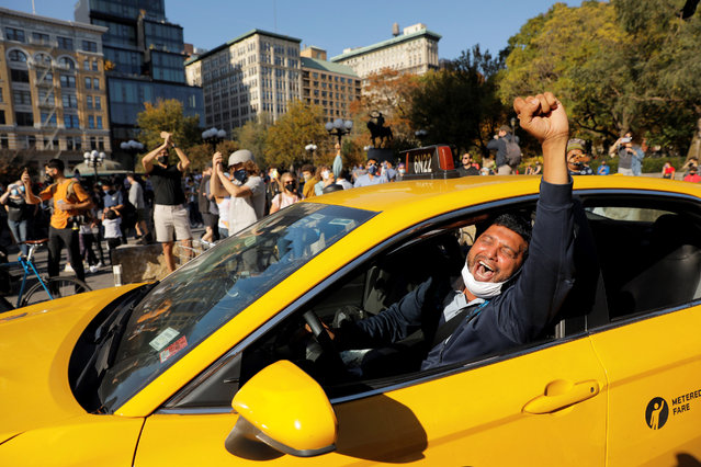 A cab driver raises his fist as people celebrate media announcing that Democratic U.S. presidential nominee Joe Biden has won the 2020 U.S. presidential election on Union Square in the Manhattan borough of New York City, U.S. November 7, 2020. (Photo by Andrew Kelly/Reuters)