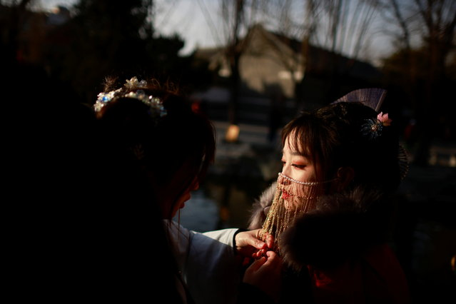 A woman adjusts the headgear of her friend's traditional hanfu dress in Daguanyuan Park as China celebrates Lunar New Year of the Ox following an outbreak of the coronavirus disease (COVID-19) in Beijing, China, February 15, 2021. (Photo by Thomas Peter/Reuters)