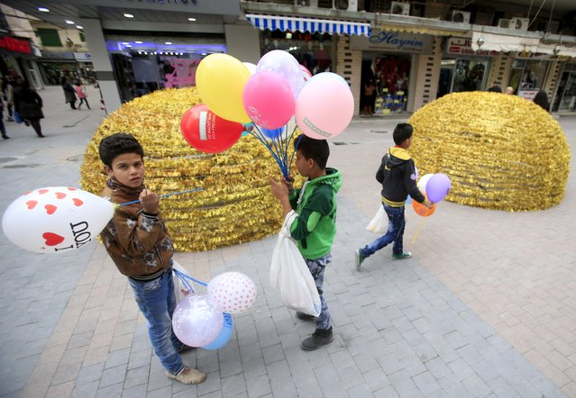 Children carry balloons near decorations set up ahead of the birthday of Prophet Mohammed in Sidon, south Lebanon December 19, 2015. (Photo by Ali Hashisho/Reuters)