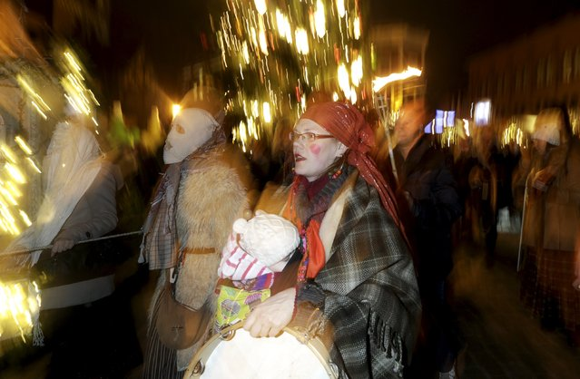 People wear costumes as they participate in the ancient Yule Log dragging tradition during winter solstice celebrations in Riga, Latvia, December 21, 2015. (Photo by Ints Kalnins/Reuters)