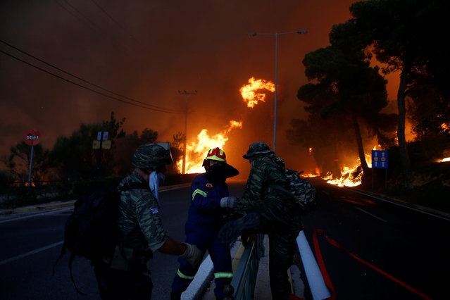 Firefighters and soldiers fall back as a wildfire burns in the town of Rafina, near Athens, Greece, July 23, 2018. (Photo by Costas Baltas/Reuters)