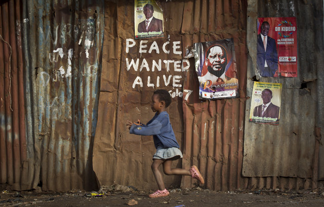 A young girl runs past pro-peace graffiti written during the post-election violence of the previous election in 2007 and a poster of presidential candidate Raila Odinga, center-right, in the Kibera slum of Nairobi, Kenya Wednesday, March 6, 2013. (Photo by Ben Curtis/AP Photo)