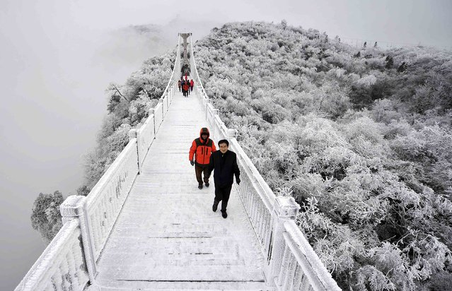 Tourists walk on a bridge covered by frosty fog on the Tianmen Mountain resort in Zhangjiajie, Hunan province, January 29, 2015. (Photo by Reuters/Stringer)