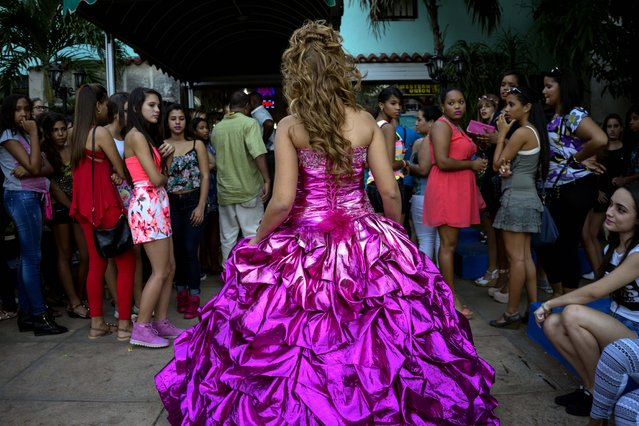 In this December 13, 2015 photo, girls watch Amanda Teresa Betancourt, who lives in Cuba, during her quinceanera photo shoot with EstudiosMayer in Havana, Cuba. (Photo by Ramon Espinosa/AP Photo)