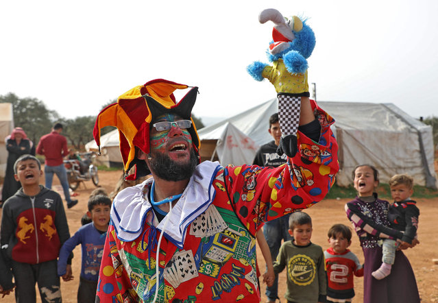Syrian comedian Firas al-Ahmad, who dresses up as a clown to entertain children in camps for displaced Syrians in the rebel-held northwest of the country, performs in the main square of a camp in Kfar Jalis north of Idlib on March 22, 2021. The 39-year-old theatre actor aims at cheering up chidlren after years of fighting and displacement in Idlib province wrought chaos for the little ones, destroying schools and scattering destitute families across the countryside. (Photo by Zein Al Rifai/AFP Photo)
