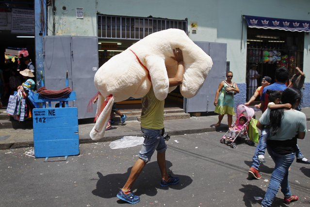 A vendor carries an oversized soft toy to be sold ahead of Valentine's Day outside the Central Market in downtown Lima February 12, 2015. (Photo by Enrique Castro-Mendivil/Reuters)