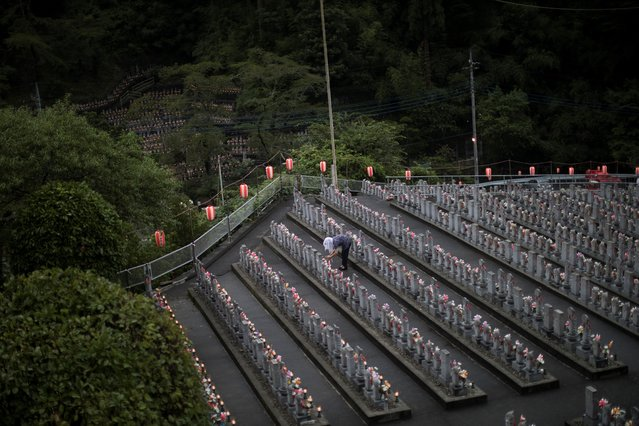 In this picture taken on August 13, 2018 a woman lights a candle in front of jizo statues in Jizoji Buddhist Temple in Oganomachi, Saitama prefecture, for the souls of unborn children and those who died at a young age, during the Obon prayers period. The Jizoji temple in Ogano, northwest of Tokyo, enshrines some 15,000 jizo stone statues dedicated for the souls of those who died at a young age, including miscarried and aborted babies. Hundreds of the temple's followers and those who have donated the stone statues gather for the Obon prayer on August 13, one of the days the souls of the dead are believed to return to the world under the Buddhist teaching. (Photo by Behrouz Mehri/AFP Photo)