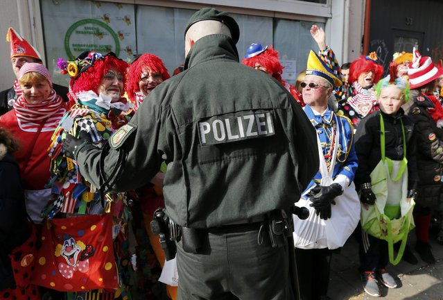 Carnival revellers talk to a police officer during the traditional Rose Monday carnival parade in the western German city of Duesseldorf February 16, 2015. (Photo by Wolfgang Rattay/Reuters)