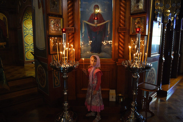 A child lights a candle during a Christmas Eve service at the Protection of the Holy Virgin Russian Orthodox Church in Sydney, Australia, 06 January 2016. The majority of the Orthodox churches worldwide celebrate Christmas on January 7, adopting the Julian calendar created under the reign of Julius Caesar in 45 BCE, electing not to use the Gregorian calendar as other Christian denominations do. (Photo by Mick Tsikas/EPA)