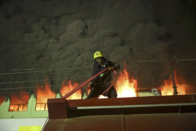 A firefighter works to extinguish a fire at Minglar market in Yangon January 9 , 2016. The cause of the fire is still under investigation. (Photo by Soe Zeya Tun/Reuters)