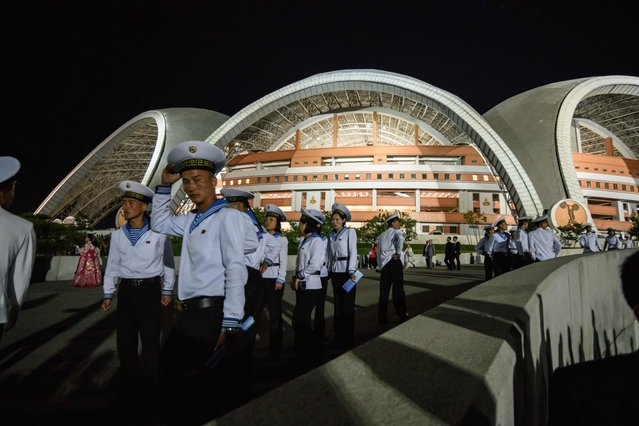 """Spectators leave following a 'Mass Games' artistic and gymnastic display at the May Day stadium in Pyongyang on September 9, 2018. The biggest show on earth made a comeback as North Korea put on its its all-singing, all-dancing propaganda display, the """"Mass Games"""", for the first time in five years. Months in the preparation, the show featured tens of thousands of performers under the curved arches of the May Day Stadium, made up of 17,490 children simultaneously turning the coloured pages of books to create giant images rippling across one side of the stadium  an analogue version, on a giant scale, of a usually digital solution to a digital demand. (Photo by Ed Jones/AFP Photo)"""