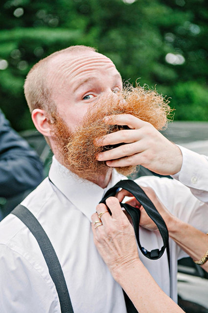 Man lifts beard to have his tie sorted. (Photo by Erica Ferrone/Caters News Agency/ISPWP)