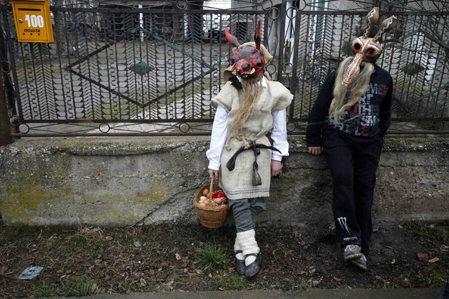 Children wearing masks take a rest in front of a house during Bele Poklade carnival celebrations in the village of Lozovik, some 100 km (62 miles) from the capital Belgrade, February 22, 2015. (Photo by Djordje Kojadinovic/Reuters)