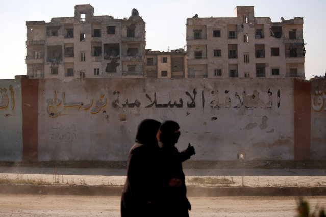 """Women walk near damaged buildings in government controlled Hanono housing district in Aleppo, Syria December 4, 2016. The calligraphy on the wall reads """"The Islamic Caliphate is Shining light"""". (Photo by Omar Sanadiki/Reuters)"""