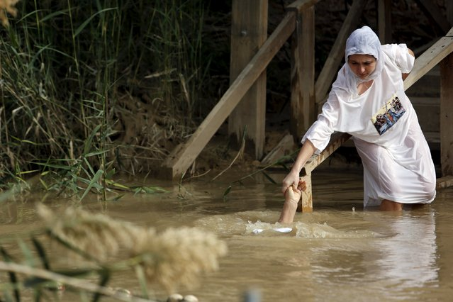 A Christian pilgrim holds the hand of her friend as they dip into the Jordan River on the Jordanian bank, at the baptismal site known as Qasr el-Yahud near the West Bank city of Jericho January 18, 2016. Thousands of Orthodox Christians flocked to the Jordan River to celebrate the feast of the Epiphany at the traditional site where it is believed John the Baptist baptised Jesus. (Photo by Nir Elias/Reuters)